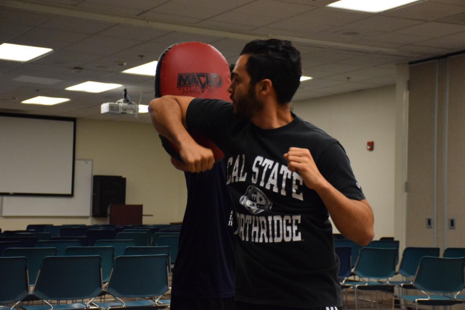 Edward Murillo, Enrollment Services staff, practices using his elbow as a body weapon to protect oneself during an attack from behind during the personal safety and awareness training Oct. 25.