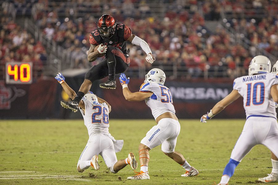 Senior running back Rashaad Penny hurdles two Boise State defenders during SDSU's 31-14 loss to the Broncos on Oct. 14.