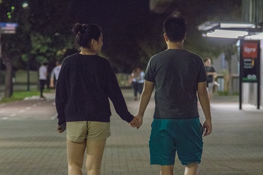 Sylvia Zhou and Tim Xu hold hands outside San Diego State trolley station.