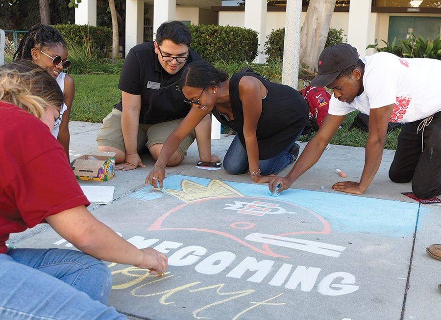SDSU+students+Cha+Cha+Rane%2C+Abel+Mercado%2C+Kimberly+Alli+and+Victor+Uwakwe+take+part+in+the+%E2%80%9Cchalking%E2%80%9D+homecoming+event+at+the+Cal+Coast+Credit+Union+Open+Air+Theatre+Oct.+16.