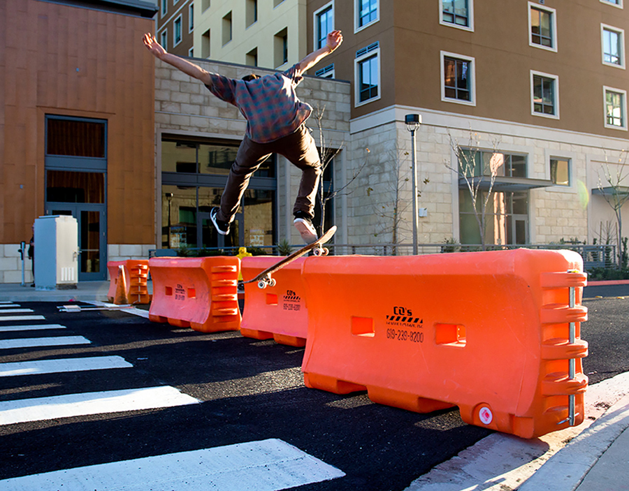 A skateboarder attempts to hop a traffic barrier near South Campus Plaza.