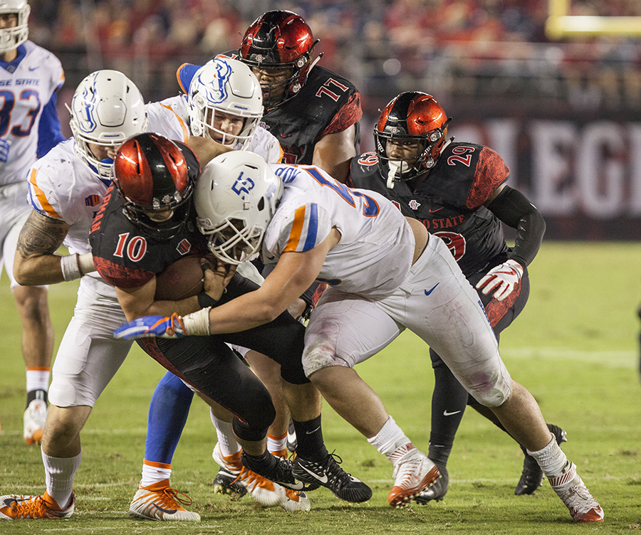 A herd of Bronco defenders converge on redshirt junior quarterback Chirstian Chapman during SDSU's 14-31 loss to Boise Sttae on Oct. 14. Chapman was sacked four times by the Broncos.