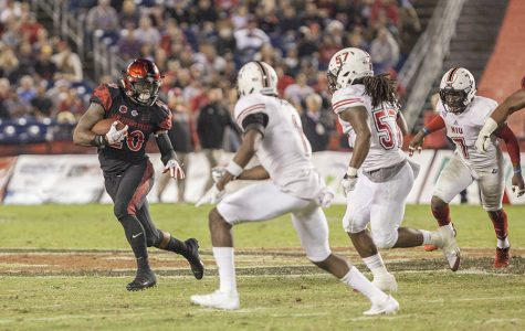 Senior running back Rashaad Penny avoids two NIU defenders during a run during SDSU's 34-28 win on Sept. 30.