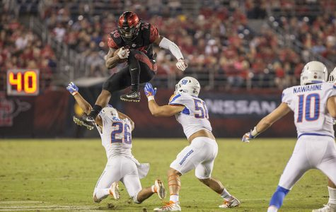 Senior running back Rashaad Penny leaps over Boise State defenders during the Aztecs 31-14 loss on Saturday, Oct.14, at SDCCU Stadium.