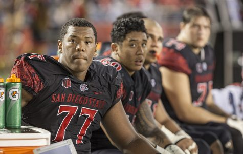 Junior offensive lineman Ryan Pope (77) and redshirt freshman Keith Ismael (60) look on from the bench during the Aztecs 27-3 loss to Fresno State.
