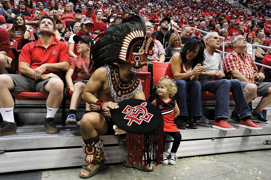 Aztec mascot sits with fans in the stands.