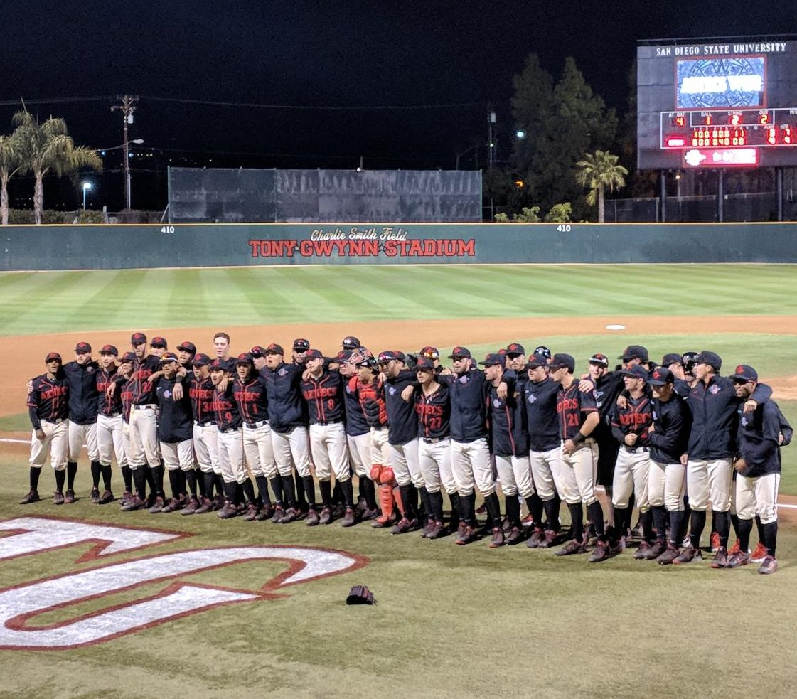 Aztecs players sing the fight song after defeating Michigan 4-3 on Feb. 26 at Tony Gwynn Stadium.