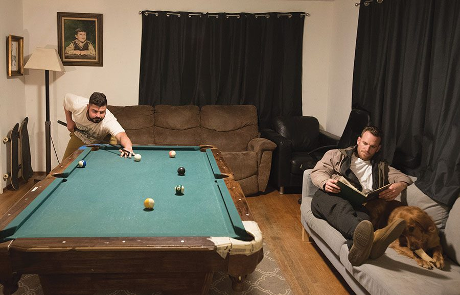 Chase Schlein and Victor Karagiozov relax in their living room.
