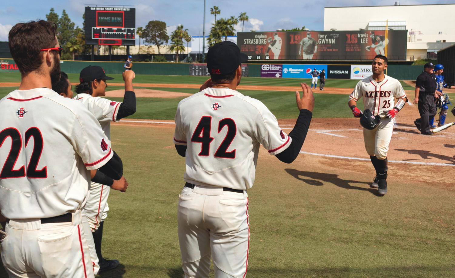 Junior catcher Dean Nevarez heads back to the dugout to celebrate with his teammates after hitting a home run during the Aztecs 3-2 victory over Air Force on March 11 at Tony Gwynn Stadium.