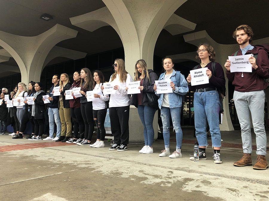 Estudiantes se paran en una línea, mostrando carteles que tienen los nombres de los quienes fallecieron en el tiroteo de Florida.