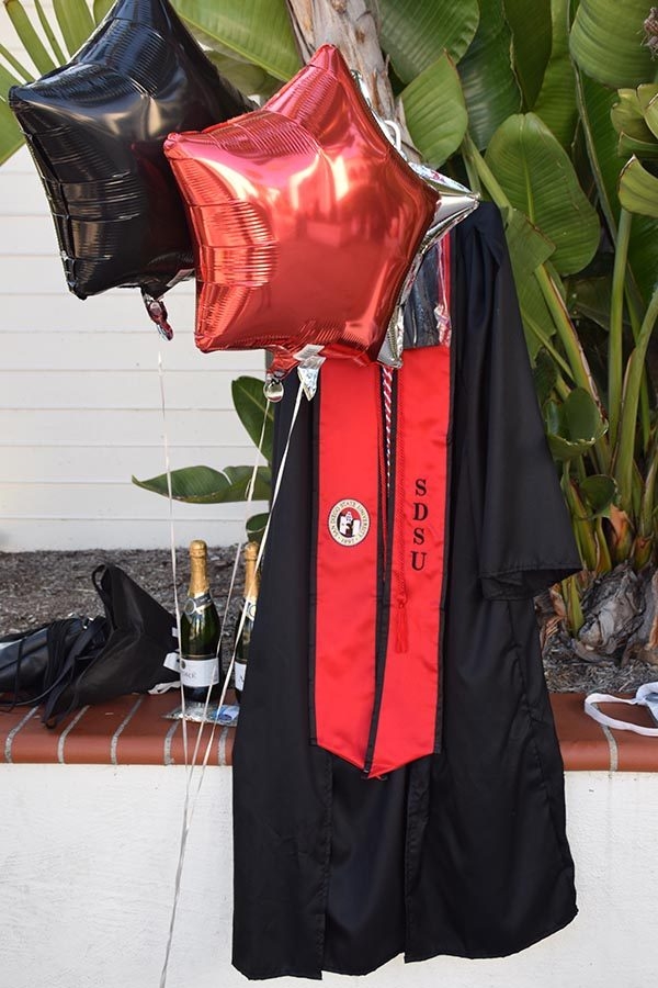Champagne, confetti, balloons and a graduation gown near Hepner Hall.