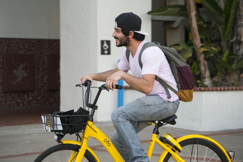 Electrical engineering junior Adam Jabbar rides an Ofo bike near Hepner Hall on April 10.