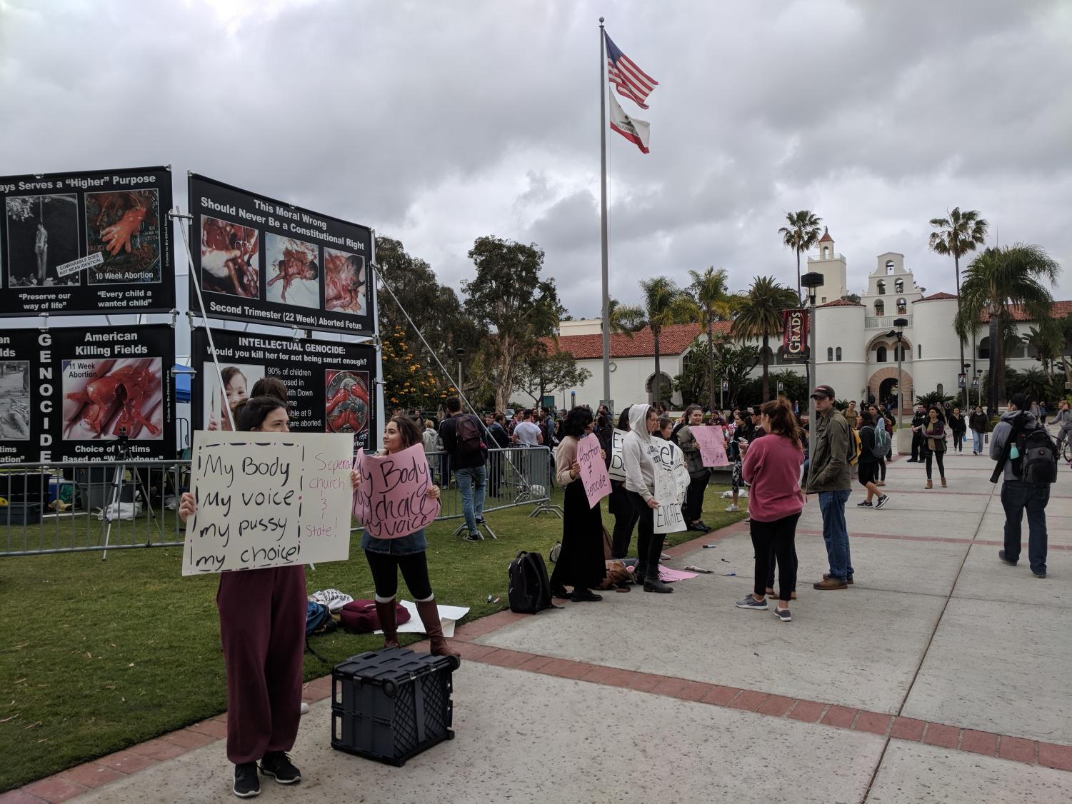 Students gather in front of a graphic anti-abortion display in the middle of campus.