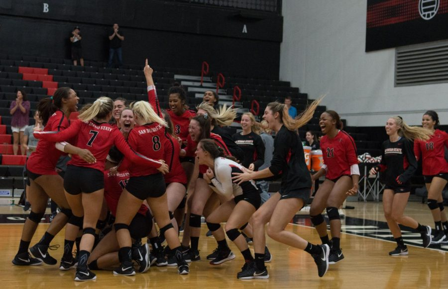 The Aztecs storm the court after defeating Wyoming in five sets on Sept. 29 at Peterson Gym. The win snapped a 13-game losing streak for SDSU.