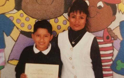 Antonio Márquez, junto con su mamá, recibe un diploma en la primaria.