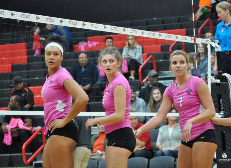 Senior middle blocker Deja Harris (left), junior setter Delaney Taylor (middle) and junior outside hitter Hannah Turnlund (right) look to the sideline for instruction during their loss against UNLV on Oct. 13 at Peterson Gym. The Aztecs wore special pink uniforms for breast cancer awareness.
