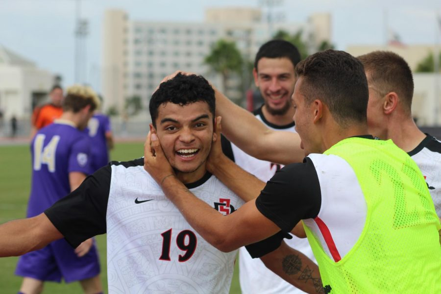 Senior forward Damian German is mobbed by teammates after assisting on a goal during the Aztecs 2-1 loss to Washington on Oct. 7 at the SDSU Sports Deck.