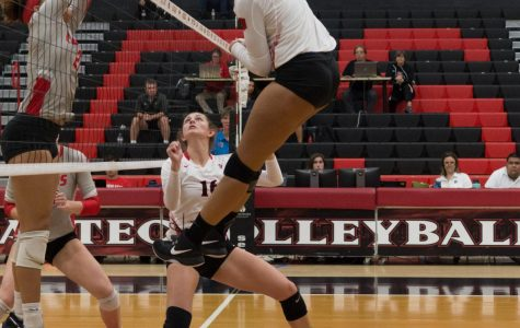 Senior middle blocker Deja Harris spikes the ball over New Mexico defenders during the Aztecs four-set victory on Oct. 11 at Peterson Gym.