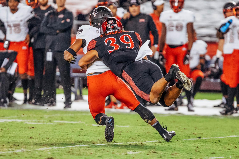 Senior linebacker Ronley Lakalaka dives to tackle UNLV quarterback Max Gilliam during the Aztecs 27-24 loss to the Rebels on Nov. 10 at SDCCU Stadium.