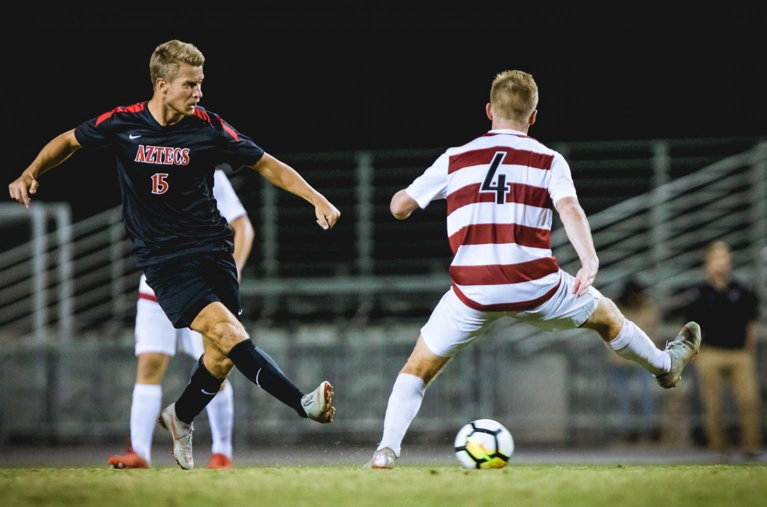 Junior midfielder Hampus Bergdahl attempts to kick the ball around a Stanford defender during the Aztecs 2-0 loss to the Cardinal on Nov. 4 at the SDSU Sports Deck.