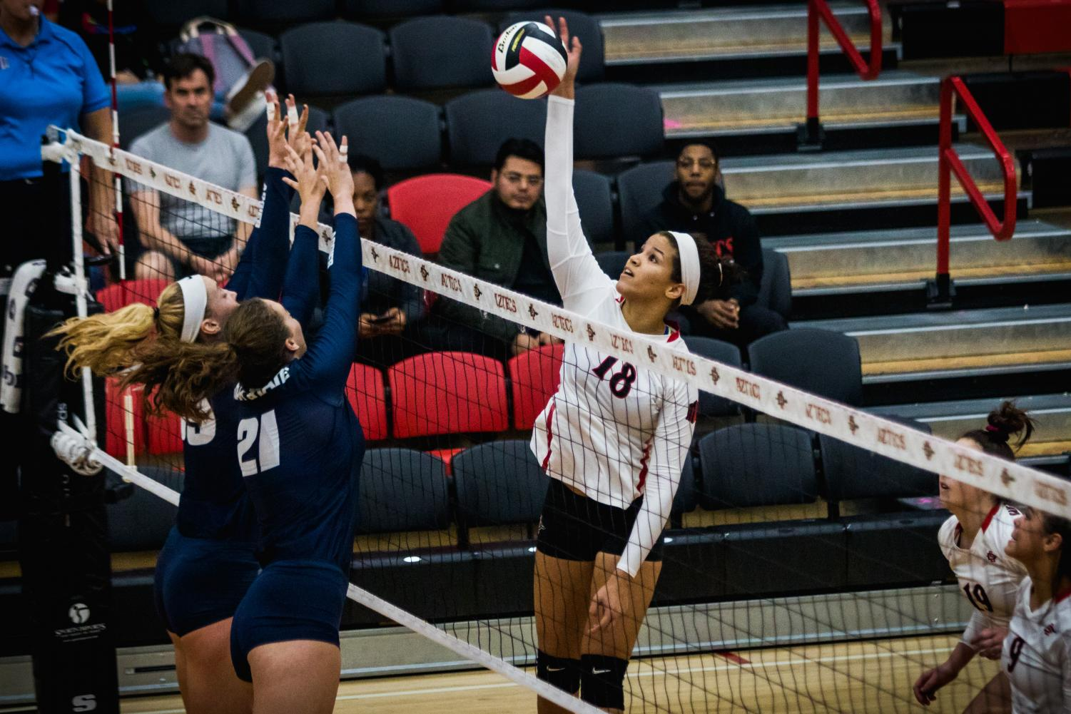 Junior middle blocker Tamia Reeves attempts to put the ball over the outstretched arms of two Utah State blockers during the Aztecs three-set victory over the Aggies on Nov. 1 at Peterson Gym.