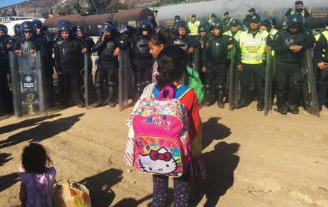 A migrant child stands in front of Mexican police in Tijuana, Mexico on Sunday, Nov. 25 during a protest at the border.