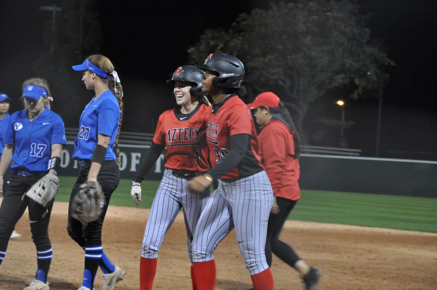 Junior outfielder Megan Smith (1) and sophomore first baseman Taylor Adams (99) celebrate after Adams drove in Smith for the walk-off run over BYU on Feb. 28 at SDSU Softball Stadium.