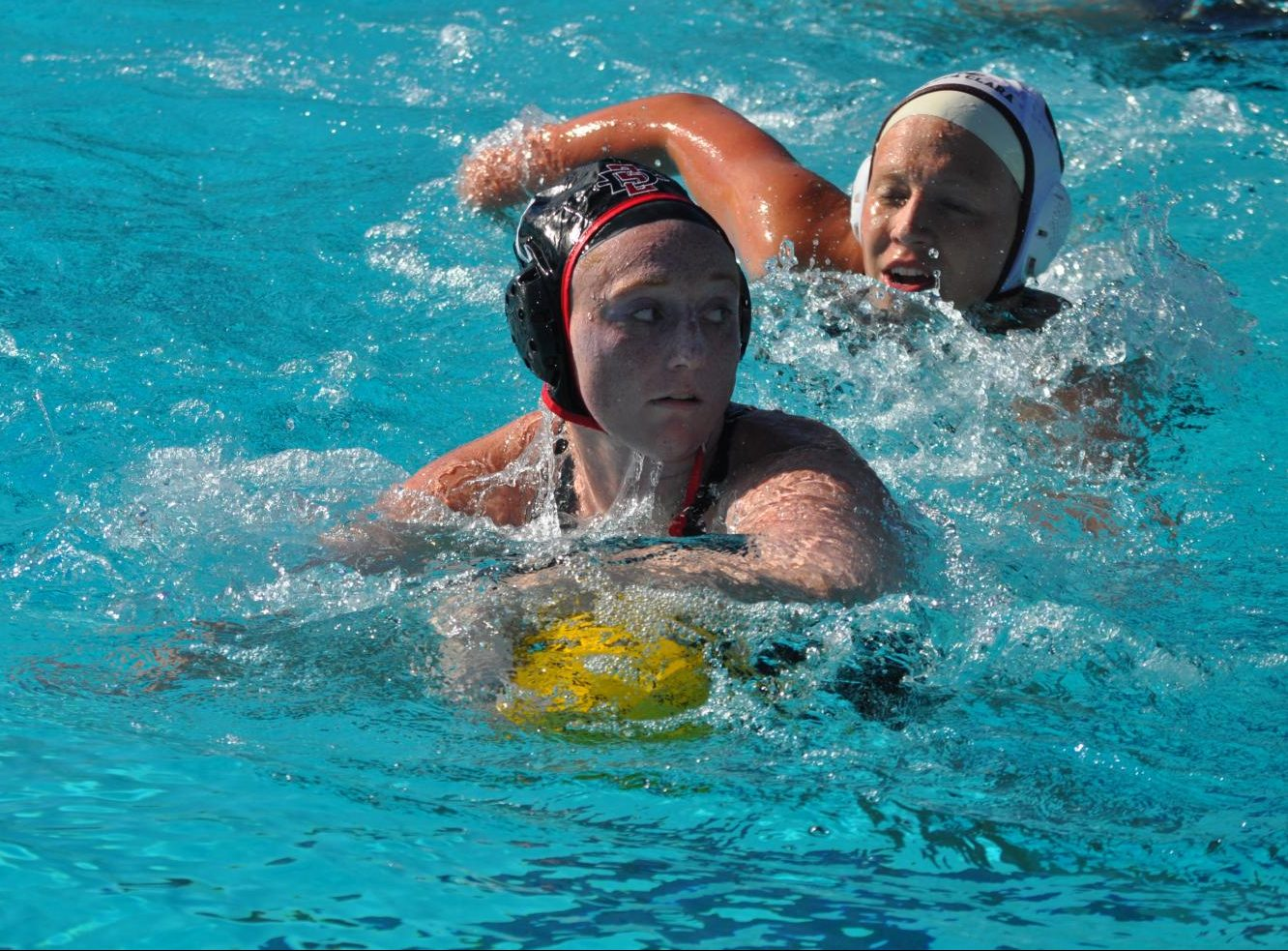 Sophomore utility player Emily Bennett keeps the ball away from a Santa Clara defender during the Aztecs' 4-1 victory over the Broncos on March 28 at the Aztec Aquaplex.