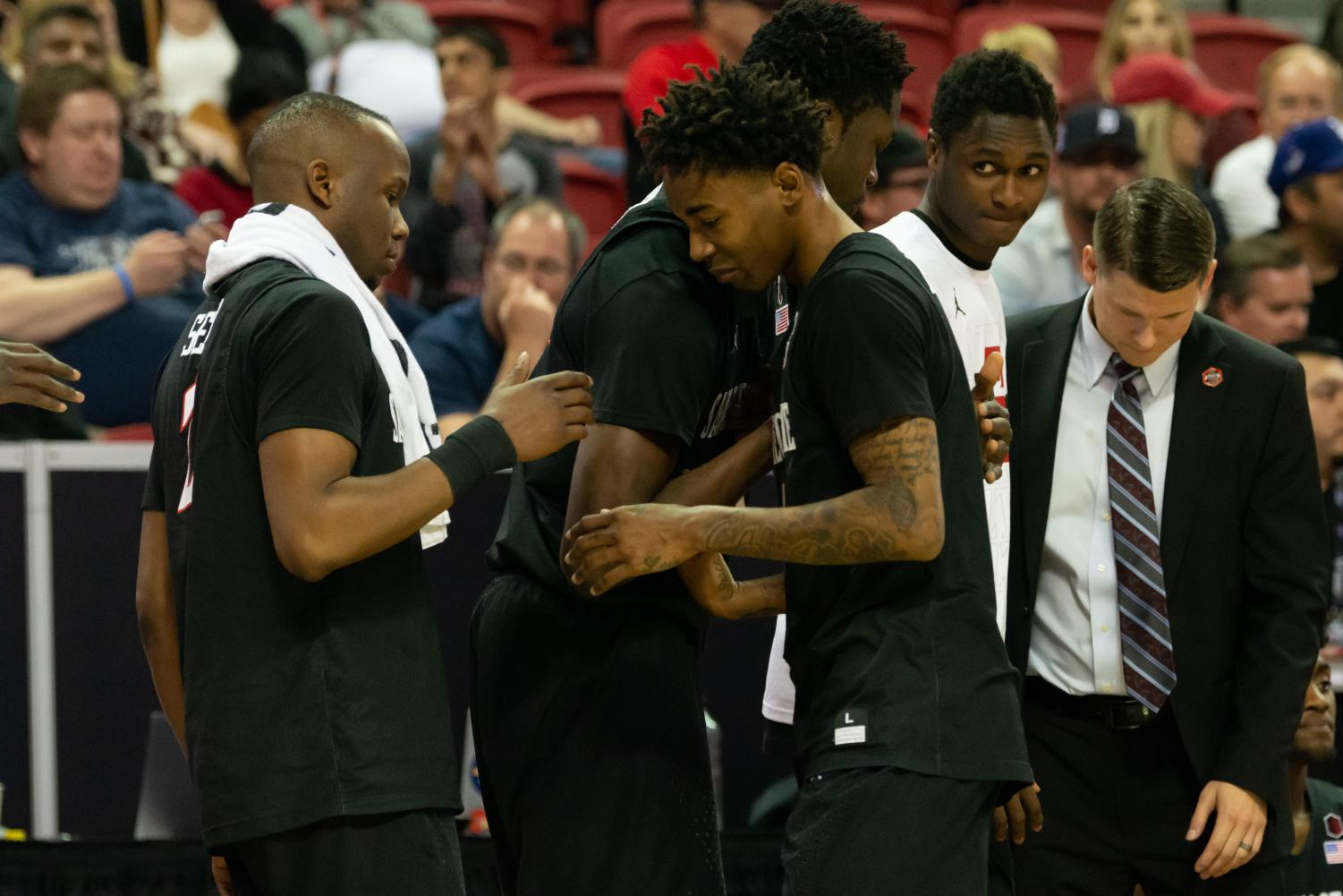 Senior guard Jeremy Hemsley embraces his teammates in the closing seconds of the Aztecs' 64-57 loss to Utah State in the Mountain West Conference tournament final on March 16 at the Thomas and Mack Center in Las Vegas.