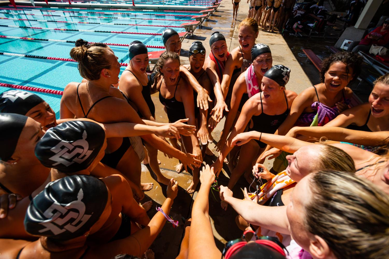 The SDSU Swim & Dive team huddles amidst competition during the 2018-19 season at the Aztec Aquaplex.