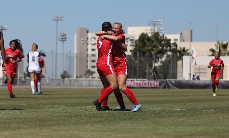 Junior midfielders Phoebe Leitch (left) and Chloe Frisch (right) celebrate a goal during the Aztecs' 4-1 win over Nevada on Oct. 6 at the SDSU Sports Deck.