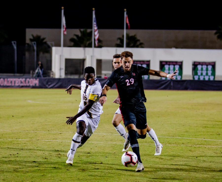 Senior midfielder AJ Valenzuela attempts to get past the Golden Bears defenders during the Aztecs' 4-0 loss to California on Oct. 10 at the SDSU Sports Deck.