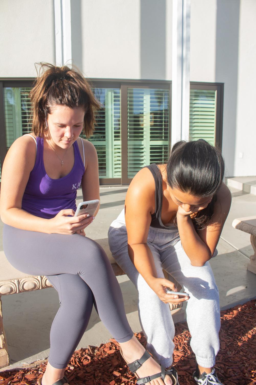 Malia Redmon (L) and Teagan DeLeon (R) using social media.