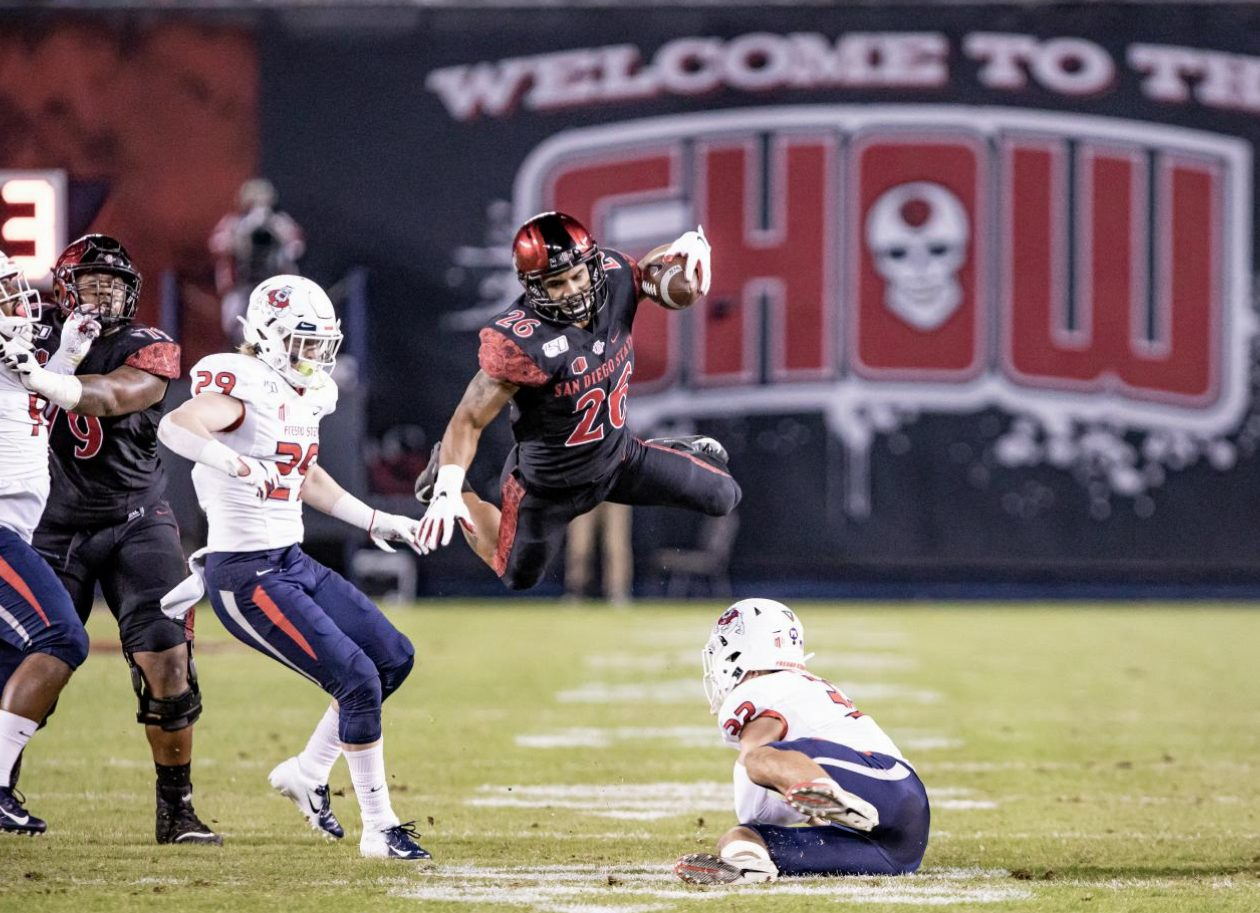 Sophomore running back Kaegun Williams attempts to go airborne for the first down during the Aztecs' 17-7 victory over Fresno State on Nov. 15 at SDCCU Stadium.