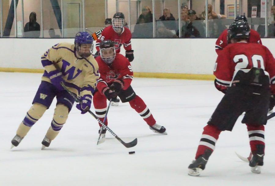 SDSU senior forward Aaron Mayer (9) attempts to take the puck away from a Washington player in the Aztecs' 6-1 win over Washington on Nov. 1 at Joan Kroc Center.