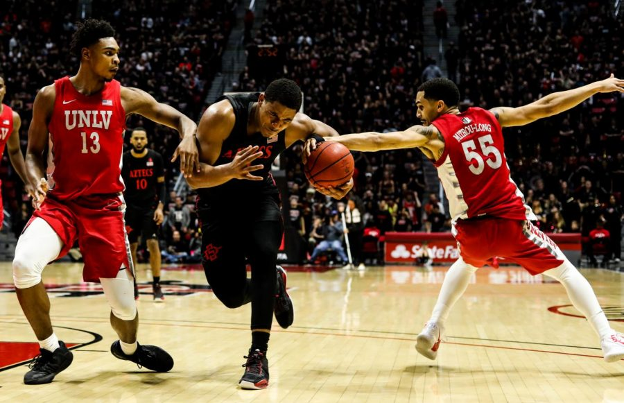 Junior guard Matt Mitchell attempts to secure the ball away from the UNLV defender during SDSUs 66-63 loss against UNLV on Feb. 22 at Viejas Arena.