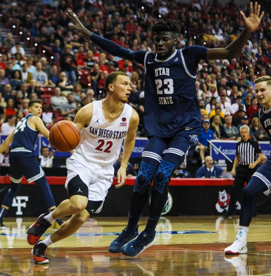 Then-junior guard Malachi Flynn dribbles past Utah State sophomore center Neemias Queta during the Aztecs' 59-56 loss against Utah State at Thomas and Mack Center on March 7.