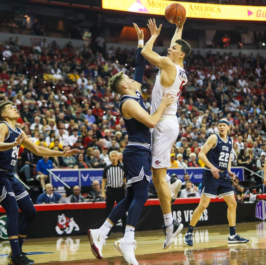 Senior forward Yanni Wetzell attempts a contested shot over a Utah State defender during the Aztecs' 59-56 loss against Utah State at Thomas and Mack Center on March 7.