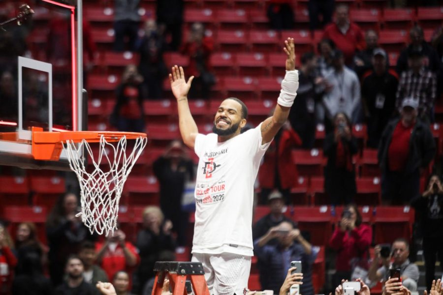 Senior guard KJ Feagin celebrates before cutting down a piece of the net after the Aztecs  82-59 win over New Mexico on Feb. 11 at Viejas Arena. With the victory, SDSU claimed the Mountain West Conference regular-season title.
