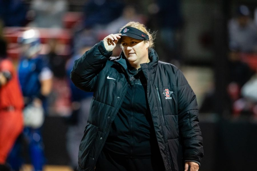 Softball head coach in waiting Stacey Nuveman Deniz adjusts her visor during the Aztecs' 3-0 win over Brigham Young on Feb. 15 at SDSU Softball Stadium.