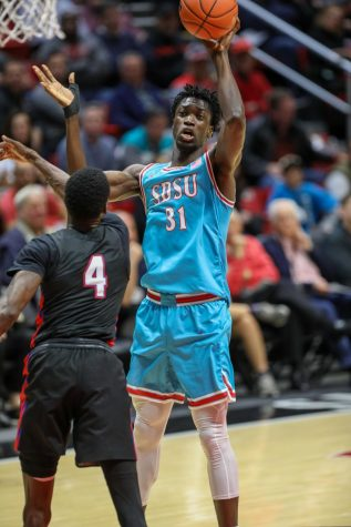 Then-sophomore forward Nathan Mensah attempts a one-handed shot over a Tennessee State defender during the Aztecs