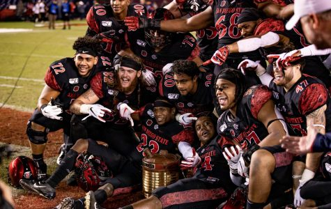 Members of the 2019 SDSU football team pose in celebration with the Old Oil Can trophy after the Aztecs' 17-7 victory over Fresno State on Nov. 15, 2019 at SDCCU Stadium. The win over the Bulldogs marked the first time the Old Oil Can was in SDSU's possession since 2016.