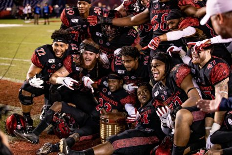 Members of the 2019 SDSU football team pose in celebration with the Old Oil Can trophy after the Aztecs' 17-7 victory over Fresno State on Nov. 15, 2019 at SDCCU Stadium. The win over the Bulldogs marked the first time the Old Oil Can was in SDSU