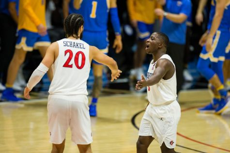 Senior guard Terrell Gomez high-fives fellow senior guard Jordan Schakel (left) during the Aztecs