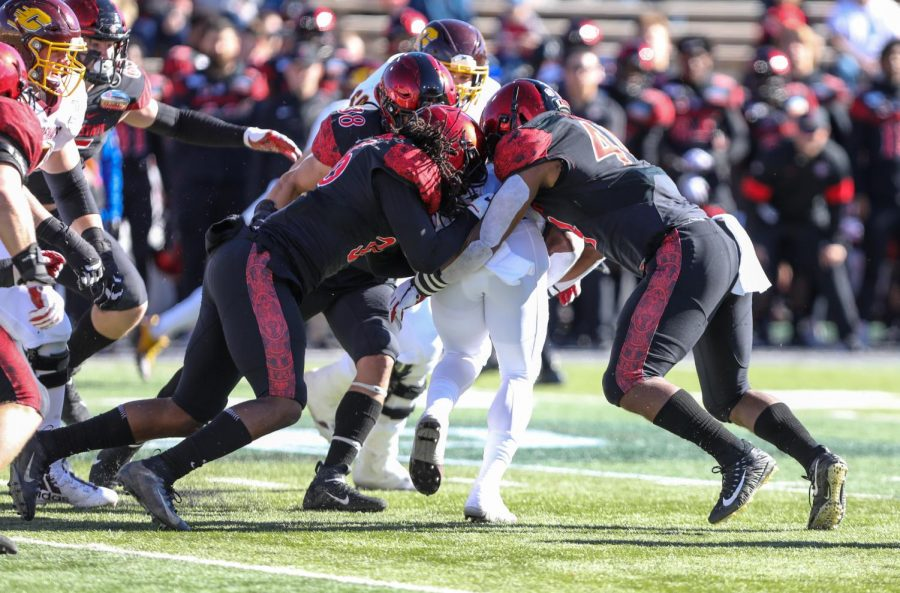 Then-junior safety Dwayne Johnson Jr., then-junior linebacker Andrew Aleki and then-senior linebacker Kyahva Tezino combine for a tackle against a Central Michigan ballcarrier during the Aztecs' 48-11 win over the Chippewas in the New Mexico Bowl at Dreamstyle Stadium in Albuquerque, New Mexico.