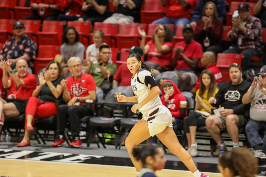 Sophomore forward Mallory Adams jogs down the court after sinking a shot during the Aztecs' 55-45 win over Cal State Fullerton on Nov. 17, 2019 at Viejas Arena. SDSU president Adela de la Torre (second from left sitting courtside) is seen clapping after the play.