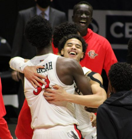 Senior guard Trey Pulliam hugs junior forward Nathan Mensah after the Aztecs