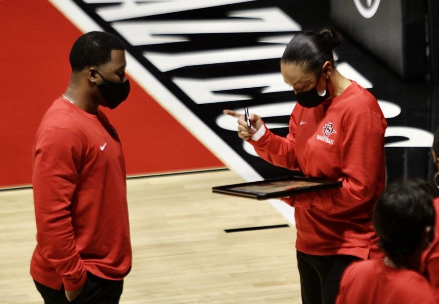 Women's basketball head coach Stacie Terry-Hutson (right) talks to assistant coach Nick Grant during a timeout during the Aztecs' 75-71 loss to Cal Baptist on Dec. 2, 2020 at Viejas Arena. All members of the women's basketball coaching staff wear athletic gear.