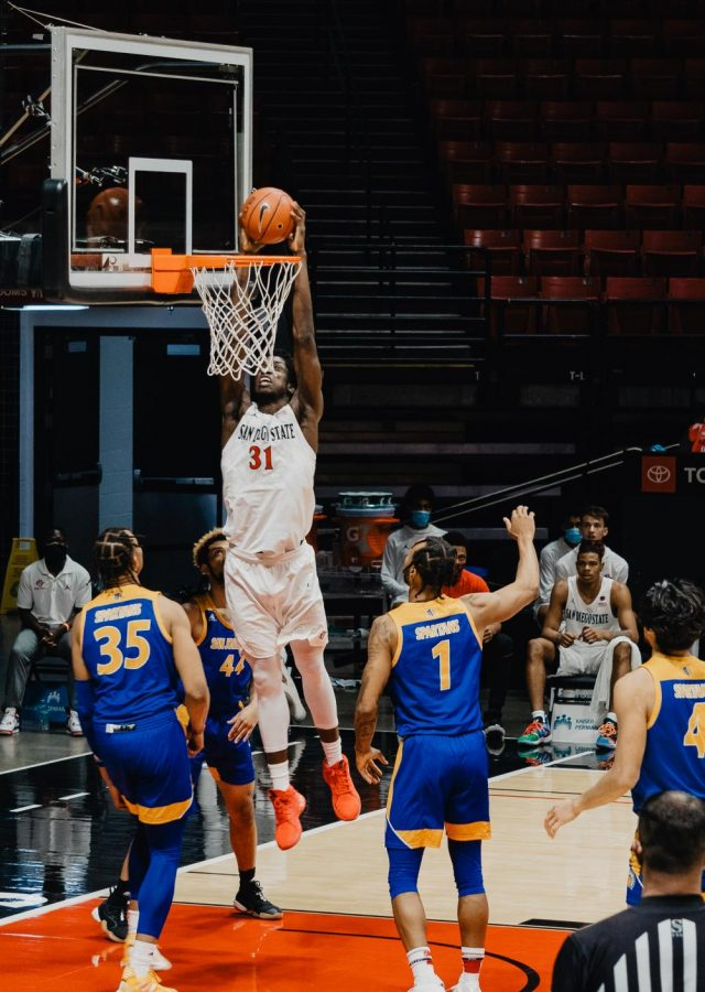 San Diego State men's basketball junior forward Nathan Mensah finishes a dunk during the Aztecs' 85-54 win over San José State on Feb. 8 at Viejas Arena.