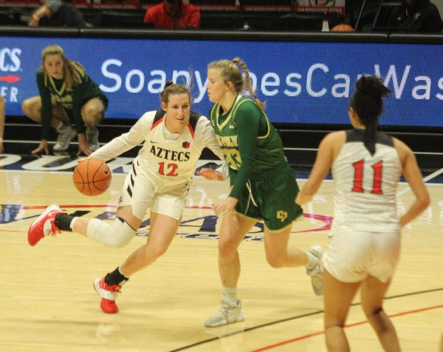 San Diego State women's basketball junior guard Mercades Staples goes against a Cal Poly defender during the Aztecs' 73-63 loss to the Mustangs on Dec. 21 at Viejas Arena.